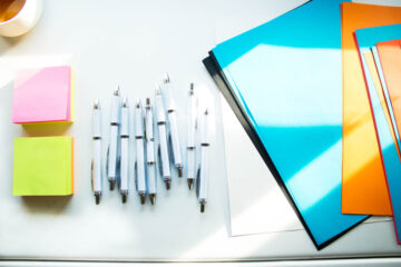 White table with piles of sticky notes, pens and folders.
