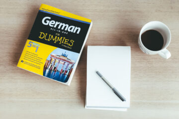 Guide on how to write bilingual characters in fiction. German language guide with a notebook and a cup of coffee on a tabletop.