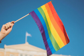 Person holding Pride flag. Post about LGBT conscious language.